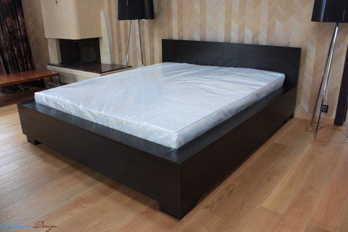 Белый матрас на коричневой кровати