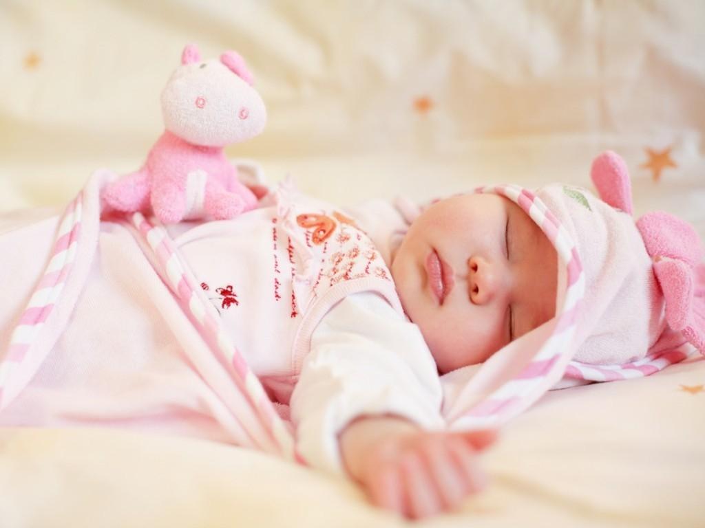 Спящая в кровати новорожденная девочка