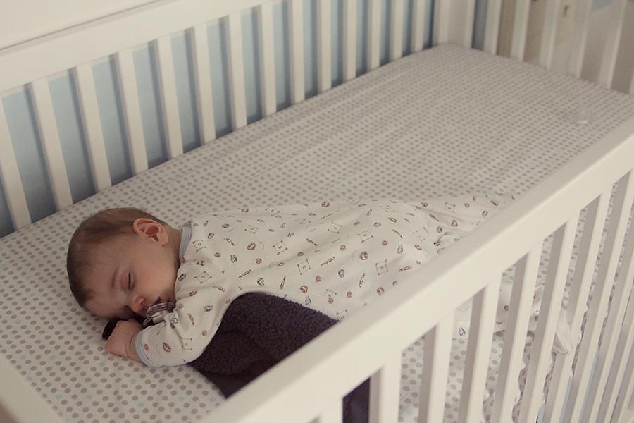 Спящий ребенок в белой кроватке
