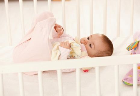 Ребенок в кроватке белого цвета