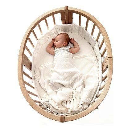 Овальная бежевая кроватка с ребенком