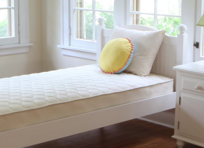 Односпальная деревянная кровать в белой комнате