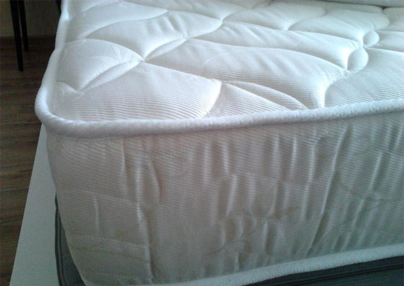 Высокий белый матрас на кровати