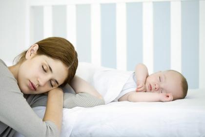 Мать со спящим в кроватке младенцем