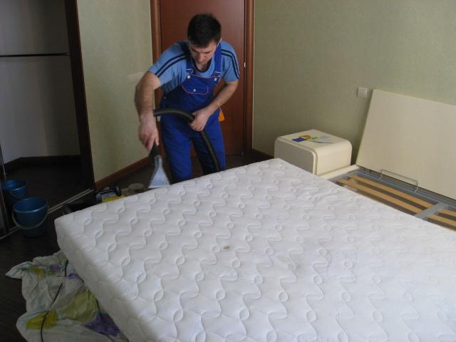 Работник клининговой службы производит химчистку матраса