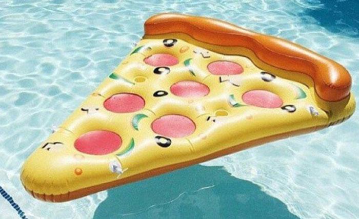 Матрас в виде куска пиццы плавает в бассейне