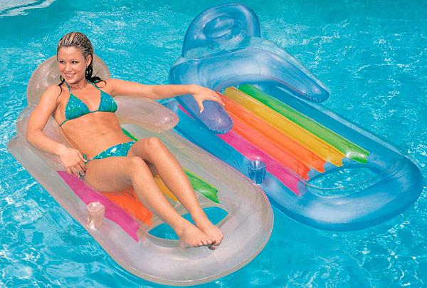 Девушка отдыхает в бассейне с двумя надувными матрасами