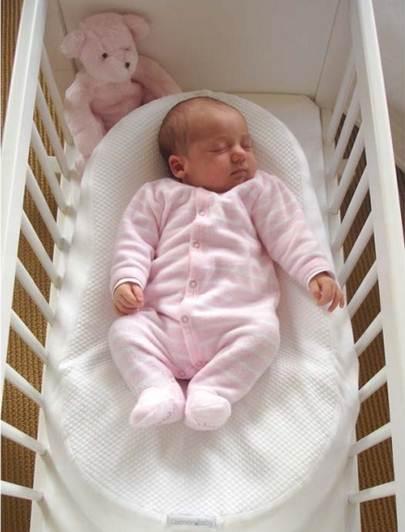 Новорожденная девочка на матрасе-коконе для младенцев