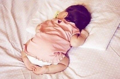 Спящий на кровати новорожденный