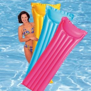 Девушка держит разноцветные надувные матрасы для бассейна