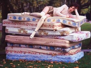 Девушка лежит на разноцветных матрасах