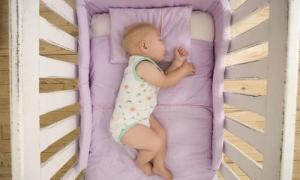 Младенец на сиреневом матрасе в кроватке