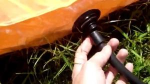 Надувание оранжевого матраса на природе
