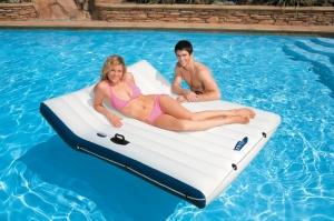 Люди отдыхают на большом надувном матрасе в бассейне