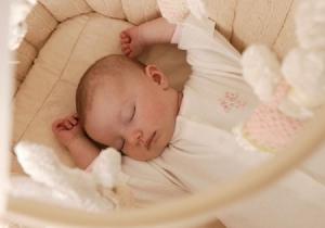 Младенец спит в кроватке на матрасе
